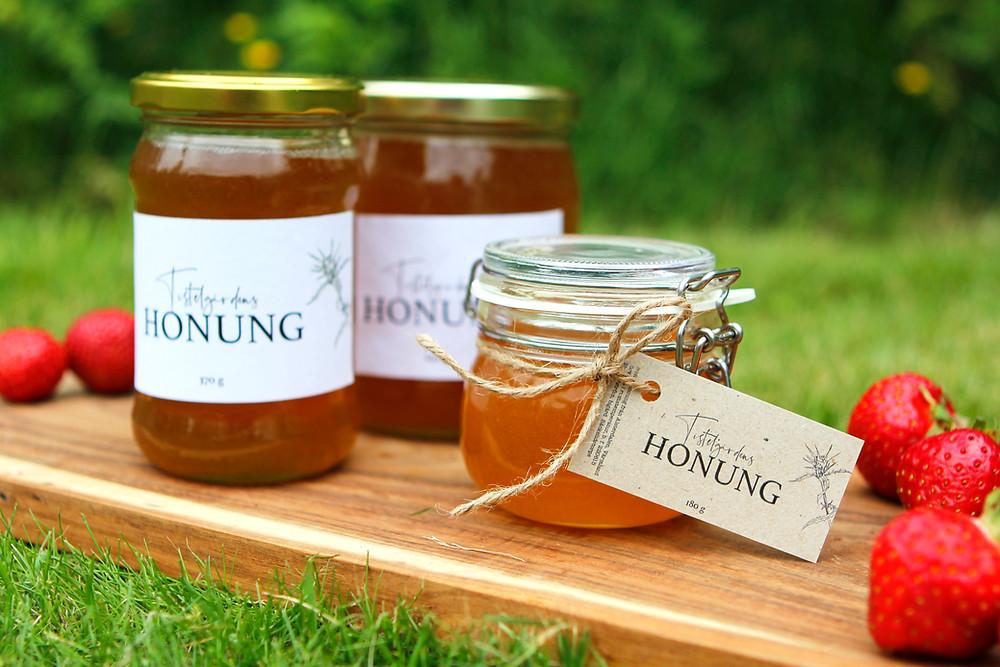 Tre olika honungsburkar på en träbricka med jordgubbar på.