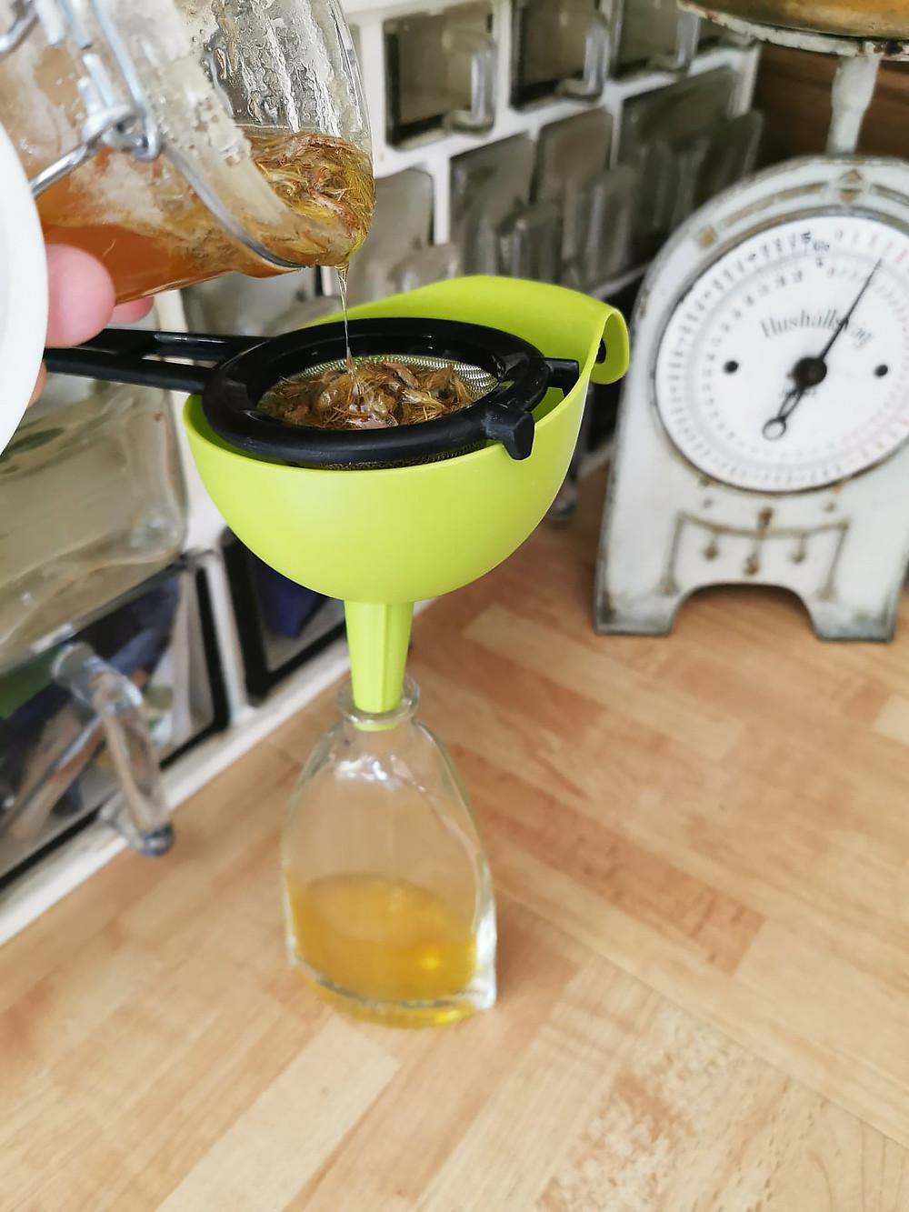 En hand häller upp sirapen genom en sil och en tratt på flaska.