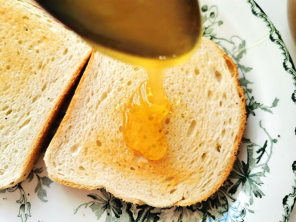 Honung ringlas ner på vitt rostat bröd.