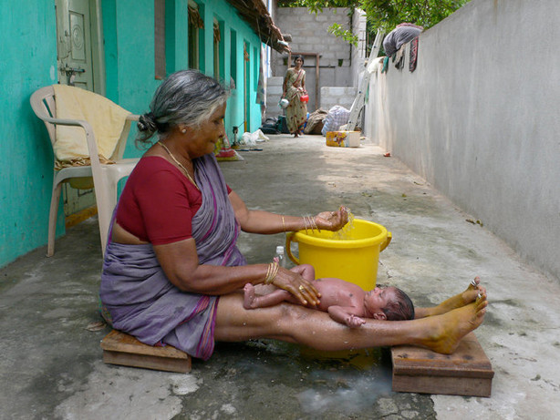 Grandmother bathing new born  in Hampi, India