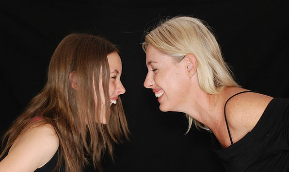 Mother and teenage daughter laughing,participatingin a Laughter Yoga activity