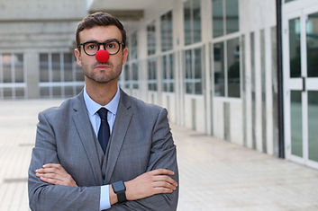 Serious looking businessman or teacher with a red nose. Laugh Therapy workshops.
