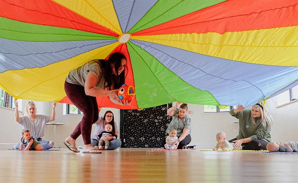 Mums and babies playing with parachute during a Baby Sparks Sensory class