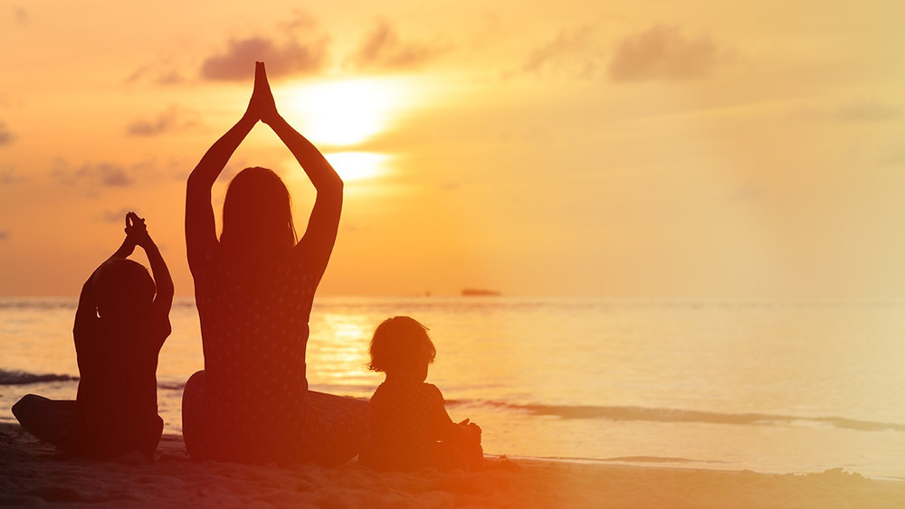 Beautiful Family meditating together on the beach