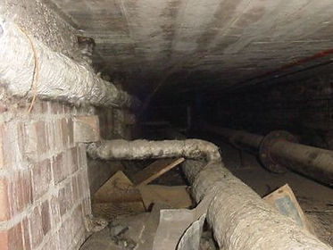 Asbestos string around non-asbestos pipe lagging in a floor duct from a type 3asbestos survey,in St Julians, Newport, 2005