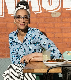 Female chef, celebrity chef Carl Hall sitting at a table of food