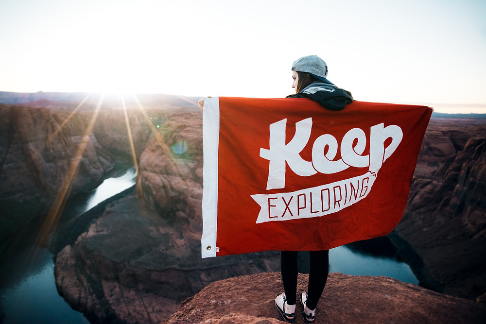"""Woman standing on a cliff with a flag that says """"Keep Exploring."""""""