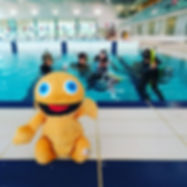 Zippy from Rainbow next to a swimmin pool with scua divers in it