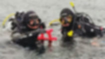 Two scuba instructors at the surface with a red dog balloon animal