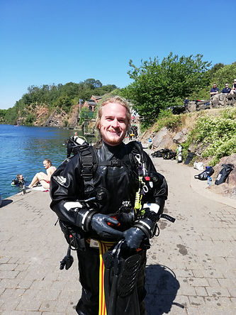 Smiling PADI Staff Instructor standing next to Stoney Cove in full scuba gear