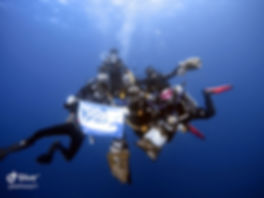PADI scuba divers underwater holding a Project Aware flag after a successful Dive Against Debris