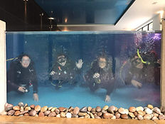PADI IDC candidats looking through a glass wall of an indoor swimming pool