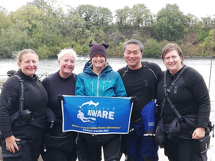 Five smiling scuba divers with a Project Aware banner