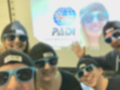 Five happy PADI Professionals in PADI hats and sunglasses, wih Regional Manager on the Skype screen in the background