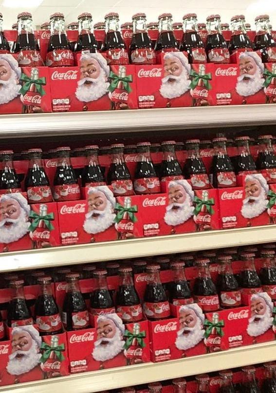 boxes of Santa Coke bottles on grocery store shelves