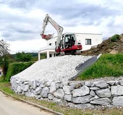Steinmauer und anschließend bereits begrünte Bewehrte Erde