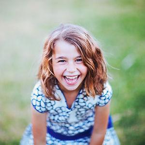 Jeune fille riant aux éclats, scène à l'extérieur.