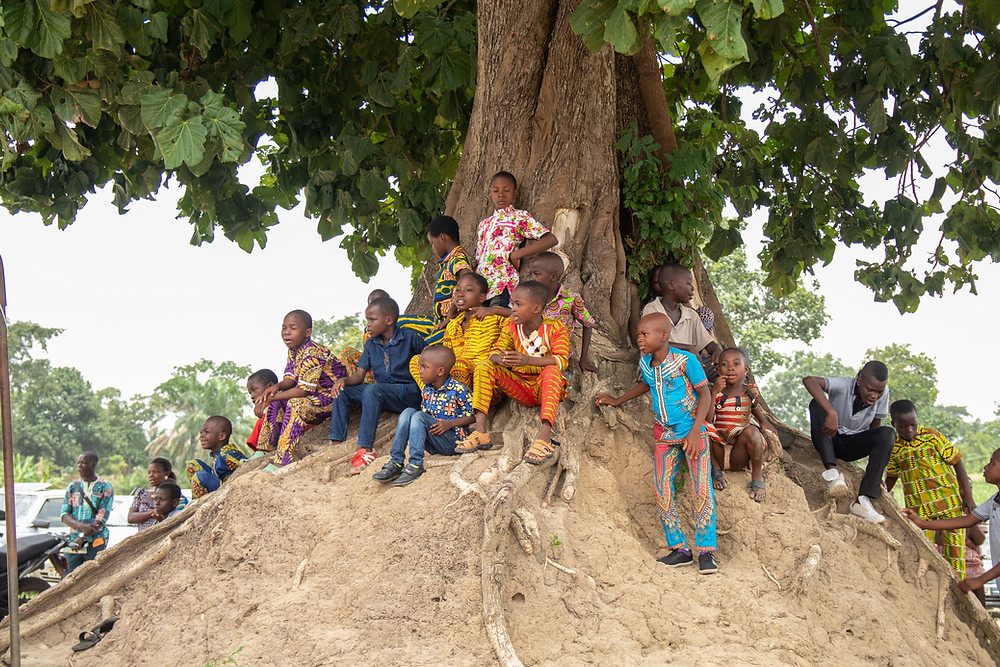 Children gather under a tree to hear the sermon Easter Sunday.
