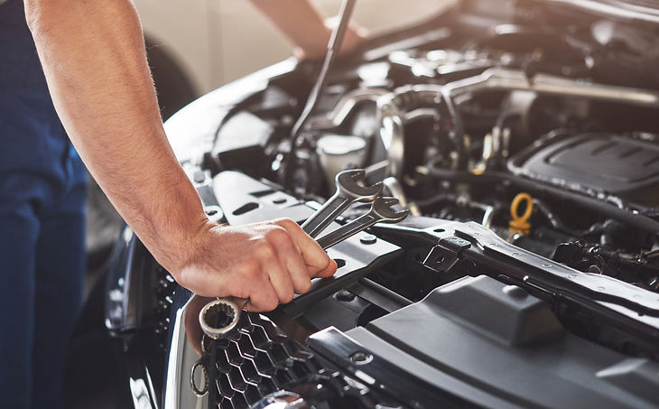 muscular-car-service-worker-repairing-ve