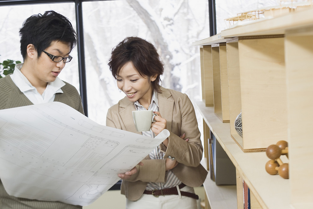 Two people looking at a large spreadsheet in a workplace setting