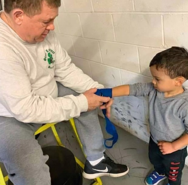 Boxing coach wrapping childs hands.jpg