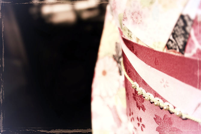 paritial close-up of woman wearing white kimono and red obi
