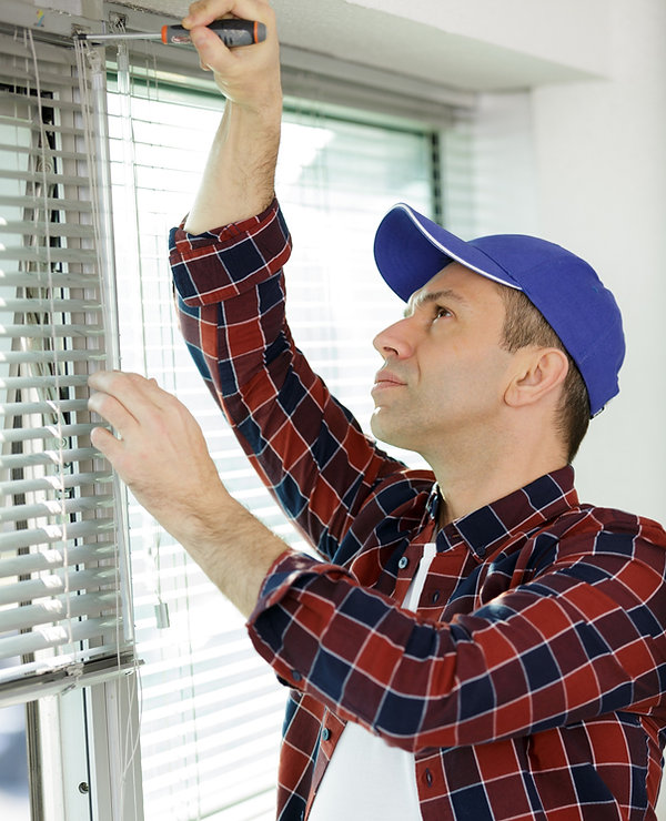 man installing window blinds in a house_