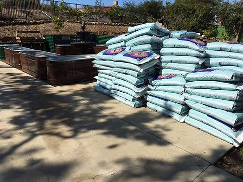 Baby Bu's Potting Soil bags in garden.JPG
