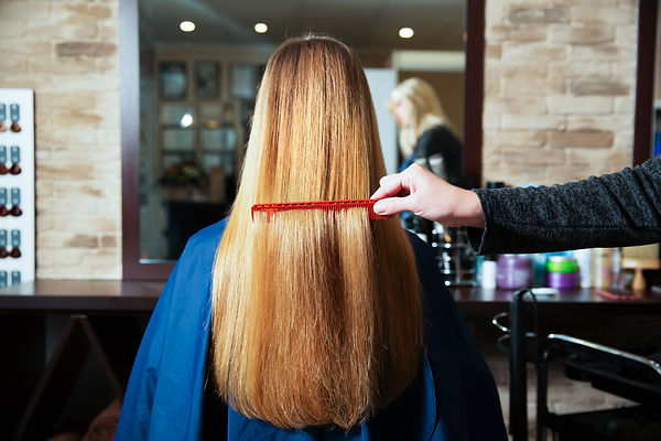 hairdresser-combs-long-hair-of-young-wom