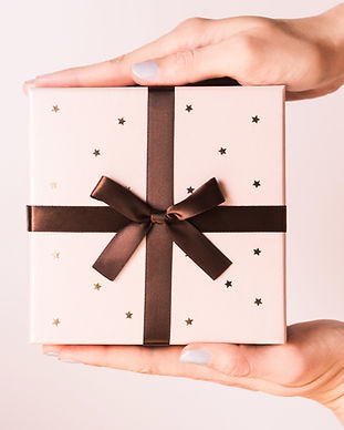 womans-hands-holding-gift-with-bow-FE38EKF.jpg