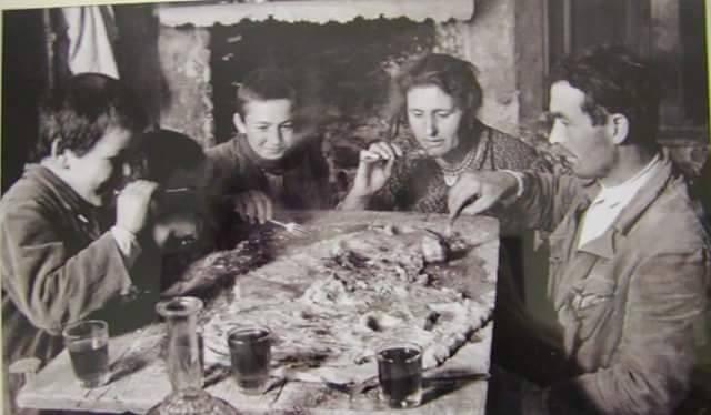 Una classica famiglia contadina di inizio secolo scorso a tavola.