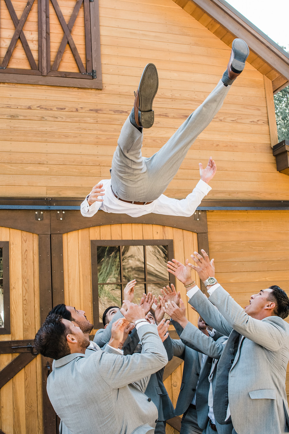 fun wedding photo - throw the groom in the air
