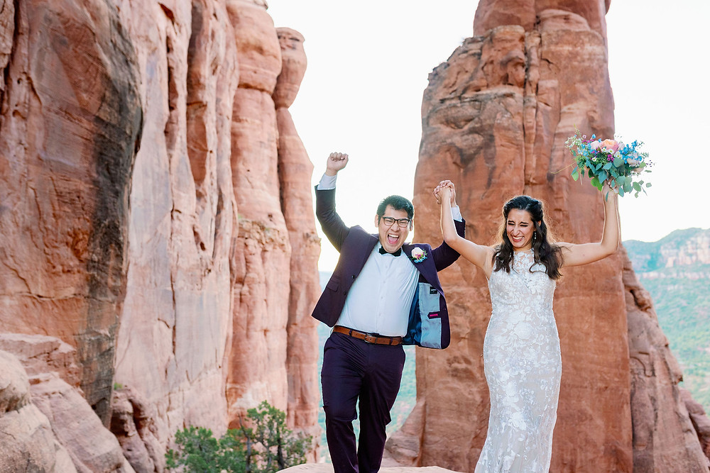 bride and groom celebrate Sedona elopement on cathedral rock at sunrise