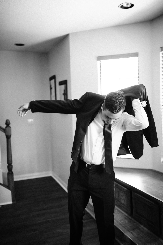 groom putting jacket on