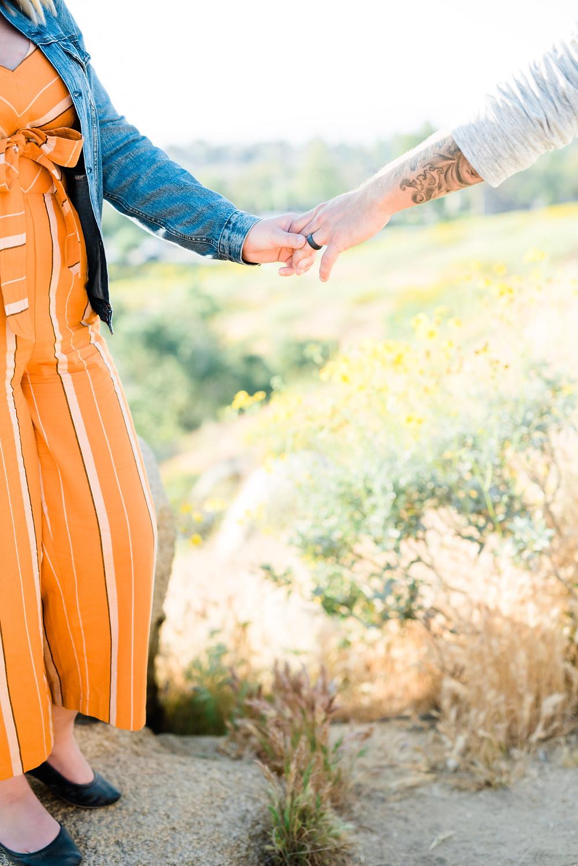 jean jacket couple session, women's orange jumper, engagement session, riverside photoshoot, holding hands