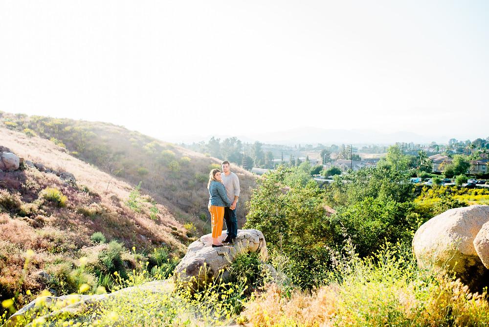 couple on rocks, riverside, women's orange jumper, women's jean jacket