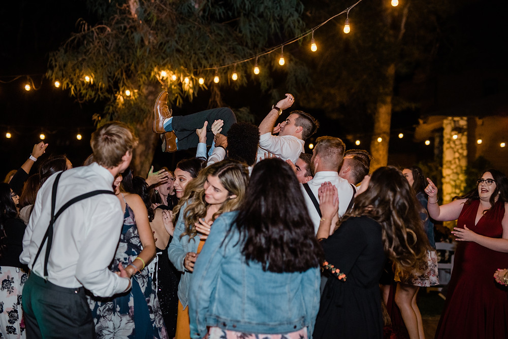 groom being carried by wedding party
