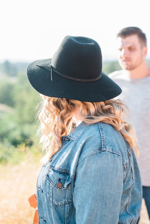 jean jacket couple session, women's orange jumper, engagement session riverside, black floppy hat