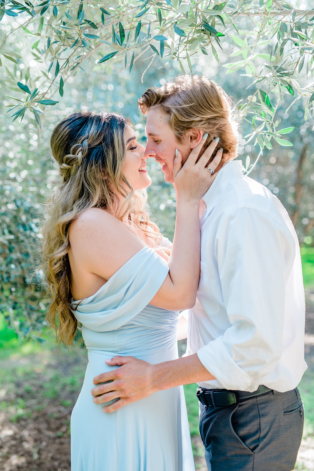 Girl holding guys face for slow kiss in olive tree in blue dress