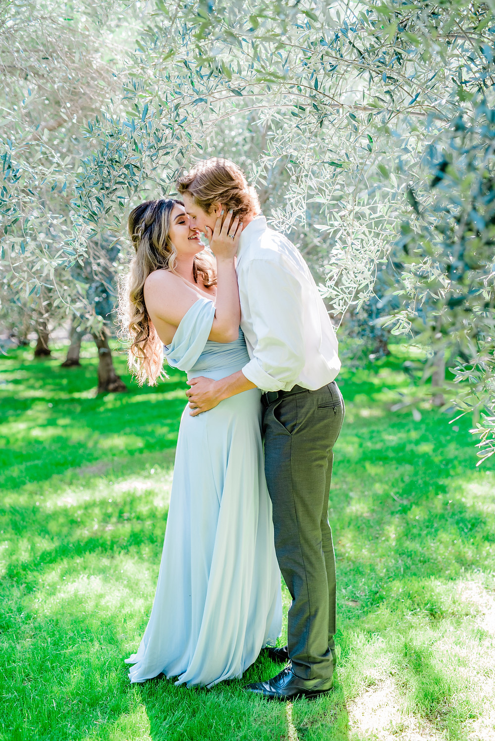Temecula olive oil company engagement photos slow kiss with off the shoulder blue dress