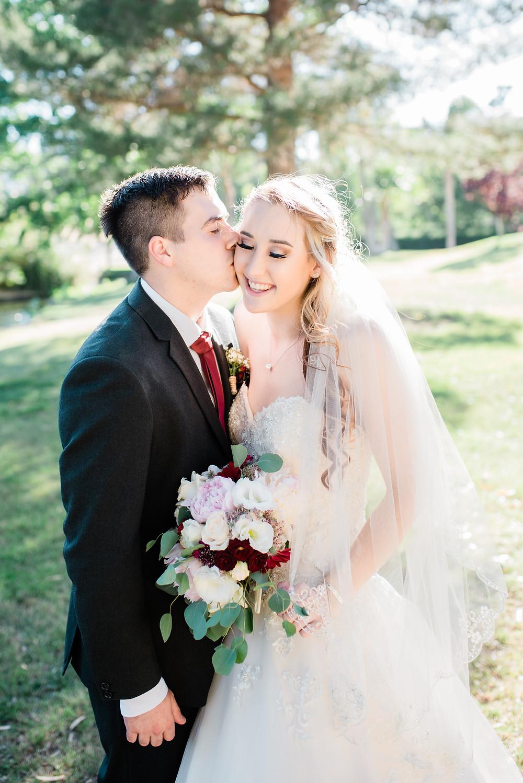 groom kisses bride on the cheek