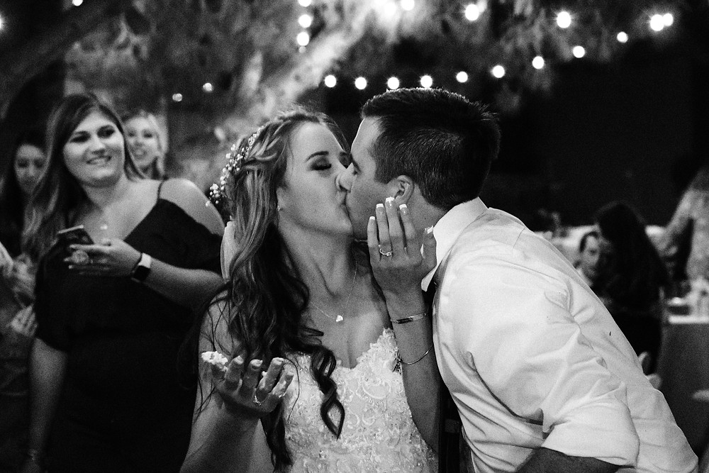 bride and groom kiss after wedding cake cutting