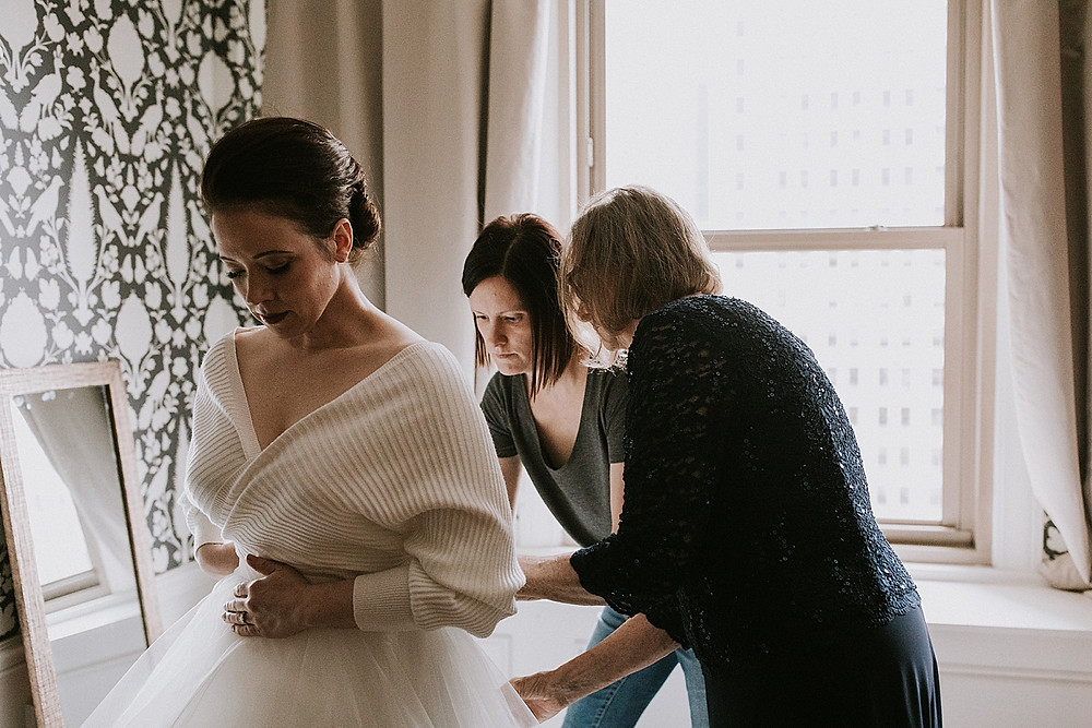 Family helping bride put on her dress before the wedding