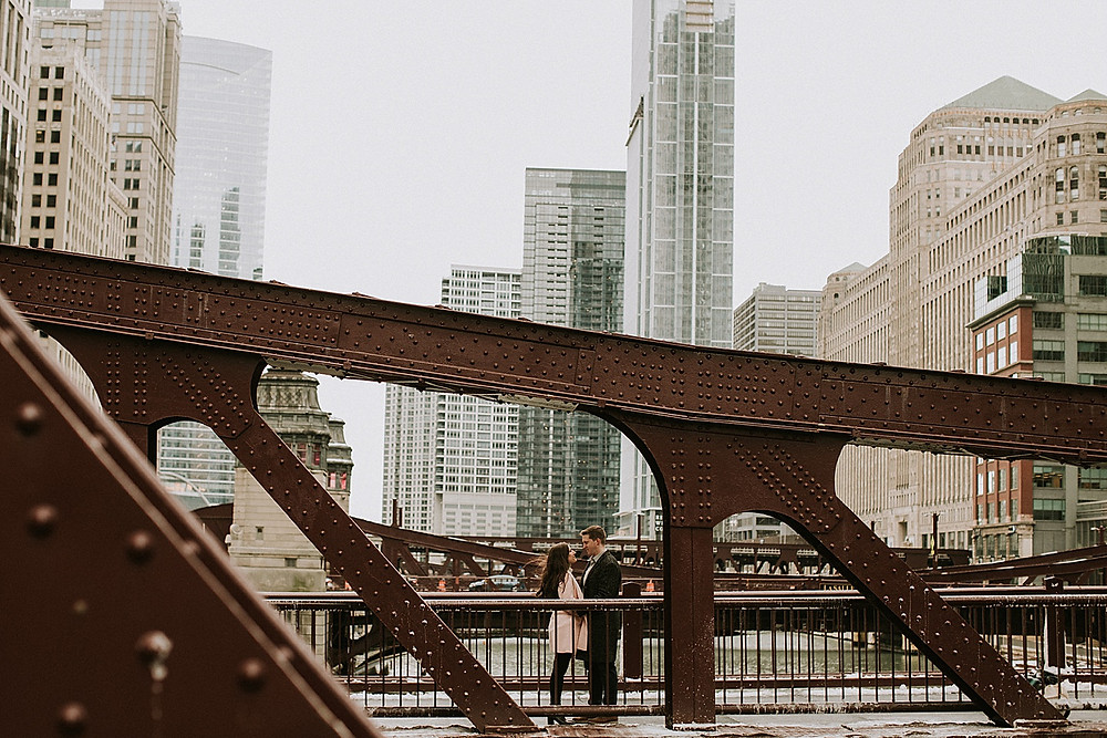 Couple standing on bridge in downtown Chicago
