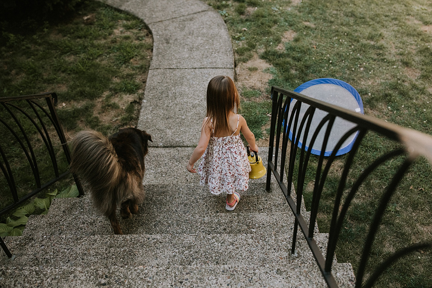 Girl carrying teapot down the stairs with a dog