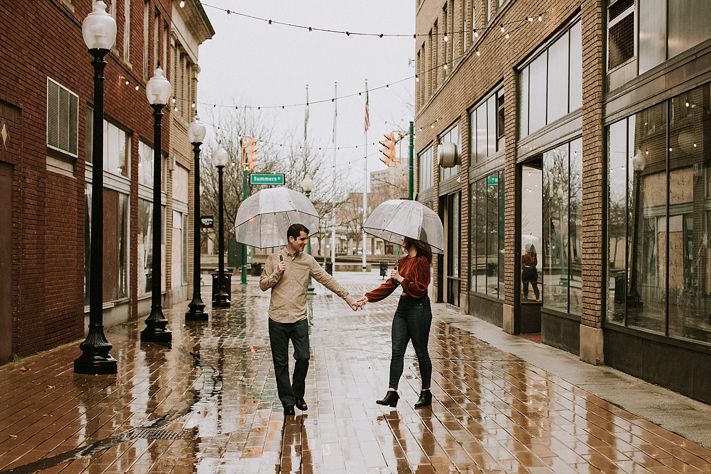 Couple walking down a brick street with umbrellas