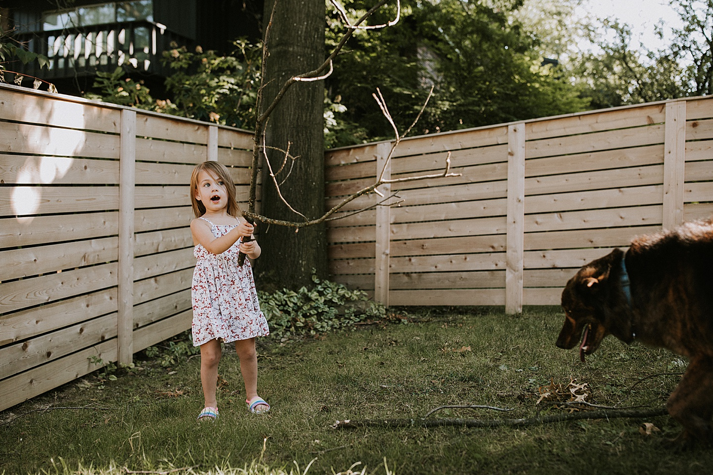 Girl holding a stick in the yard