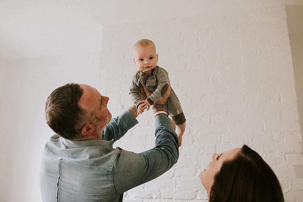 Dad holding up baby