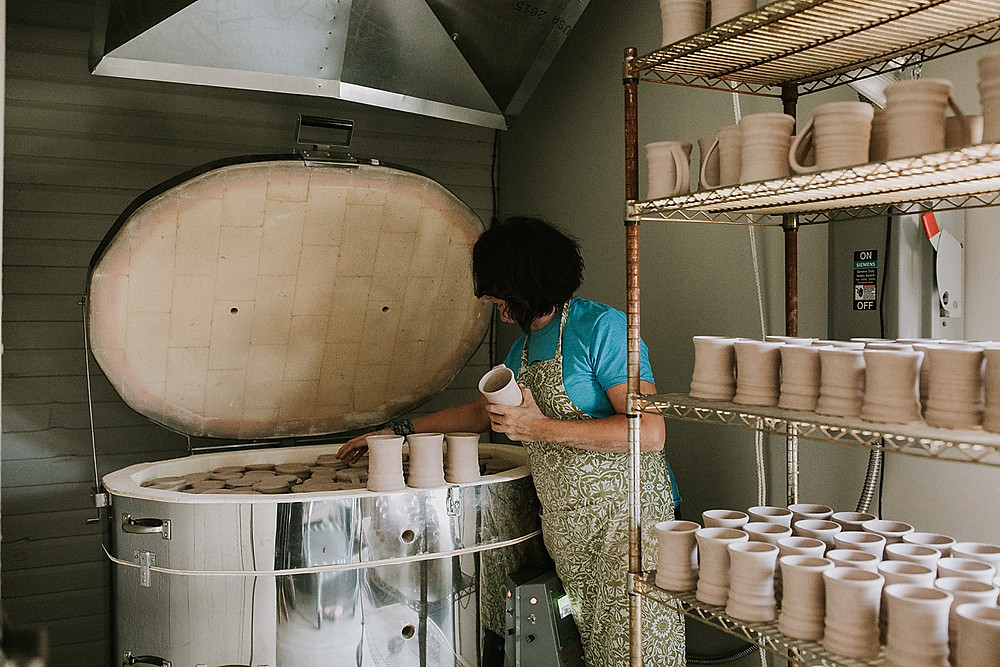 Women removing mugs from kiln