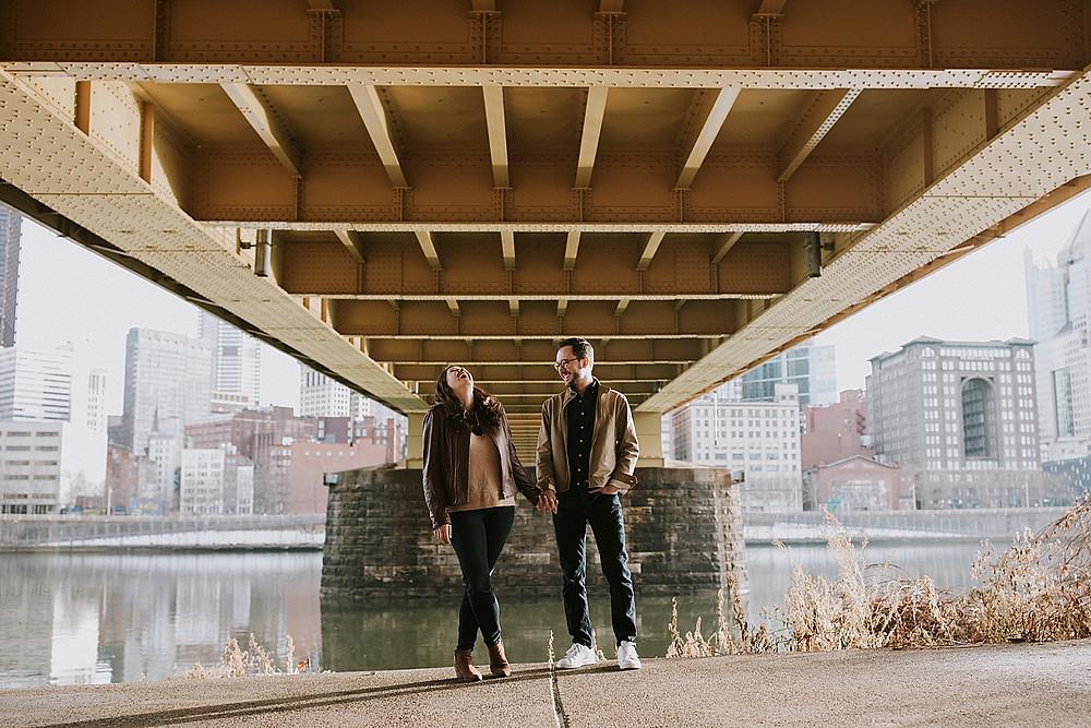 Couple laughing under Pittsburgh bridge